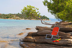 Chair on the beach rocks Royalty Free Stock Photo