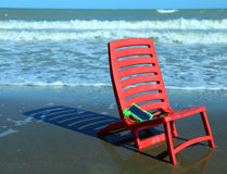 Chair on the beach with a smartphone closed in the protective wa Stock Photography