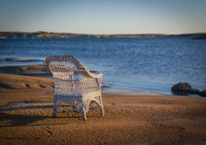Chair on beach. White chair standing on a rocky beach stock photo