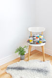 Chair with bright cushion and sheepskin rug on the floor Stock Photos