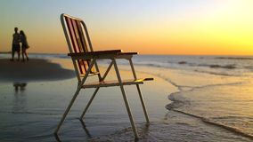 Chair on the coast in sunset with backgrounf of people silhouettes.  stock footage