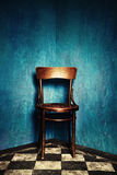 Chair in corner. Wooden chair in corner of grunge room with blue walls and tiled floor Royalty Free Stock Photography