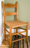 Chair in corner. Antique chair sitting in a corner where 2 color walls meet royalty free stock images