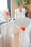 Chair covering and table setting at wedding. Focus on the back of a wedding chair and chair cover with ornamental orange daisy, and tables and bright window with Royalty Free Stock Images