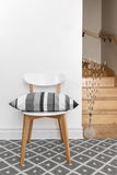 Chair with cushion in a room with staircase. Chair decorated with gray striped cushion in a room with staircase royalty free stock images