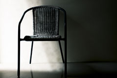A chair in dark room.concept of loneliness and waiting. Concept of loneliness and waiting. a chair in dark room Stock Image