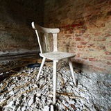 Chair on debris. A chair in an abandoned building - room interior stock images