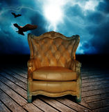 Chair on deck. An ornate leather chair on a wooden deck with lightning and birds flying in the sky.  Concept for story telling Royalty Free Stock Photography