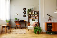 Chair at desk near armchair and wooden table in retro workspace interior with vinyl. Real photo. Conceptn stock image
