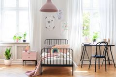 Chair at desk next to bed in pink and white girl`s room interior with plants and windows. Real photo stock images