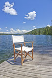 A chair on the dock of a beautiful lake. A white canvas chair on the dock of a beautiful lake with blue sky and clouds royalty free stock image