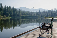 Chair on a dock. A chair is setting on a dock that is provided for people to fish off of. It is an inviting place to sit and relax and enjoy the view Royalty Free Stock Image