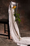 Chair with dress and rose. A chair with a white dress and a yellow long stemmed rose Stock Photography