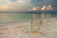 Chair on Eagle Beach in Aruba. Morning light illuminates fading storm clouds over Eagle Beach in Aruba Royalty Free Stock Photo