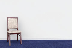 Chair in Empty grey room's wall with blue carpet Stock Photo
