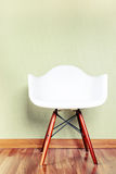 Chair in empty room against a green wall Stock Photography