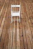 Chair and empty space on wooden floor. Single chair standing alone on wooden floor in empty room. Blank floor background. Studio stock photo
