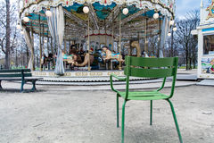 Chair facing an empty carrousel. In a park on a cloudy day Stock Photo
