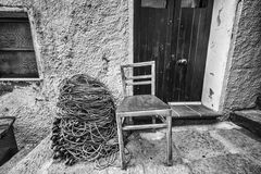 Chair and fisherman net by a rustic wall. Wooden chair and fisherman net by a rustic wall stock photos