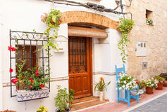 Chair and flower pots decorate home exterior in narrow Spanish t Royalty Free Stock Images