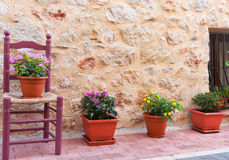Chair and flower pots decorate home exterior in narrow Spanish t Royalty Free Stock Photography