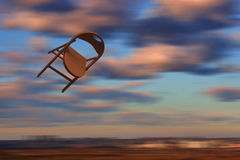 Chair flying in the sky. Yellow pink clowds Royalty Free Stock Photography