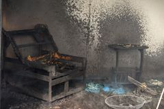 Chair and furniture in room after burned in burn scene of arson. Chair and furniture in house after burned with smoke and dust in burn scene of arson stock photo