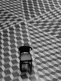 Chair on Geometric Patterned Floor. Single Chair on Geometric Patterned Floor giving an optical illusion type of feel Royalty Free Stock Photography