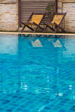 Chair on ground beside swimming pool. Day time with nobody Royalty Free Stock Photo