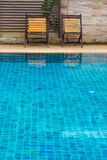 Chair on ground beside swimming pool Royalty Free Stock Photos