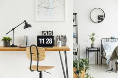 Chair by hairpin desk. Metal and wood chair standing by a hairpin desk with notebooks, tea mug, laptop and lamp stock photos