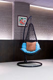 Chair hanging on a chain in the hotel lobby Stock Images
