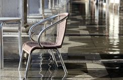 Chair at high tide under the arcades during the flood in Venice Royalty Free Stock Images