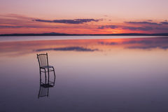Chair on a lake at sunset with beautiful colours. Chair on a lake at sunset Stock Image