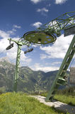Chair Lift. Mechanism of a chair lift, cable wheel with mountain and blue sky in the background Stock Images