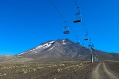 Chair lift above volcano slope covered with ash. Chair lift above Volcano slope covered with gray ash and red lava rocks Stock Photography