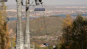 Chair lift against the city an autumn sunny day stock footage