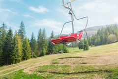 Chair lift on the background of a green coniferous forest royalty free stock images