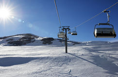 Chair-lift and blue sky with sun Royalty Free Stock Images