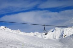 Chair lift and off-piste slope at nice day Stock Photography