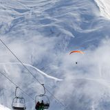Chair-lift and paraplane in haze on ski resort at cold winter da. Y. Snowy Caucasus Mountains. Georgia, region Gudauri Stock Image