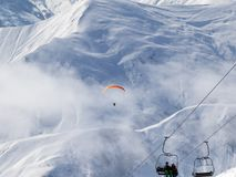 Chair-lift and paraplane on ski resort at cold winter day. Snow Caucasus Mountains in fog. Georgia, region Gudauri Royalty Free Stock Images