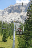 Chair lift people up towards the top of the Dolomites royalty free stock photo