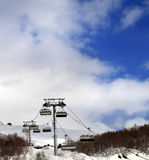 Chair lift on ski resort and snow winter mountain in clouds Royalty Free Stock Photo