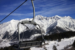 Chair-lift at ski resort and snow winter mountains in nice sun d Stock Images