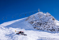 Chair lift and snow groomer in Alps. Chair lift and snow groomer at Hintertux Glacier in Zillertal Alps in Austria stock image