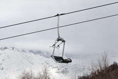 Chair lift and snowy mountains in haze Stock Photos