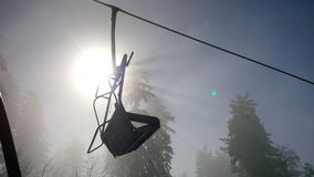 Chair lift with sun shining through fog. At Austria mountains called Alps Stock Images