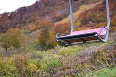 Chair lift to mountain top through Autumn surroundings Royalty Free Stock Image