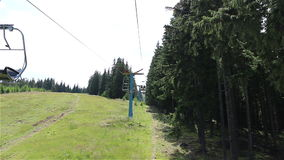 Chair Lift Travelling View. A ski lift slowly climb through pine forest in a summer sunny day. An elevated passenger ropeway, or chairlift, is a type of aerial stock footage